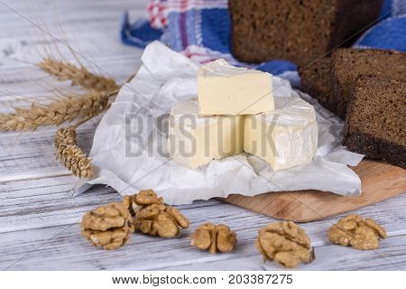 Brie cheese or camembert cheese. Fresh Brie cheese and slice on a wooden board with walnuts and black bread slice. Italian or French cheese. Close up