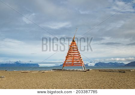 Wooden installation made of planks and driftwood. Driftwood at the beach at Svalbard with blue sky and white clouds, ocean, beach and mountains