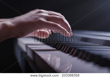 Close-up of a female hands playing piano against a black background