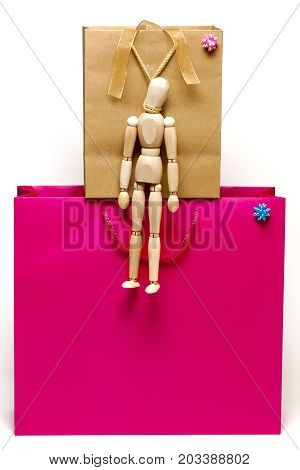 Mannequin hanging from shopping bag handle as a concept of stop shopping
