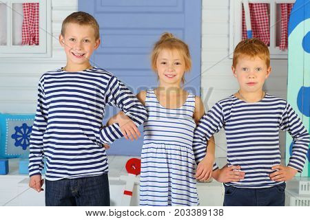 MOSCOW - OCT 04, 2016: Portrait of a happy girl and two boys (with model release) in striped costumes in front of the porch with lilac door