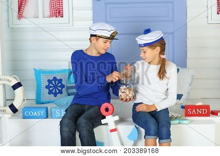 MOSCOW - OCT 04, 2016: Young girl and boy (with model release) in a cap with the inscription Admiral are looking at seashells from a glass jar sitting on the porch