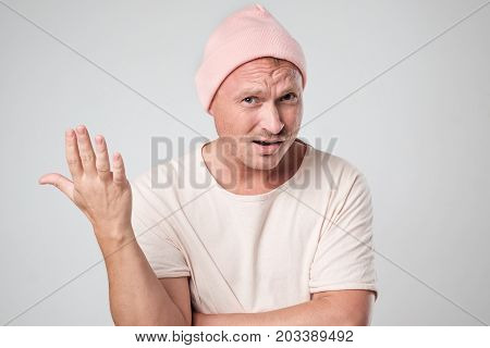 Shot of stylish young caucasian man shrugging shoulders gesturing with hands. Concept of indignant expression on face
