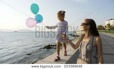 An attractive woman goes by the hand with a little beautiful girl at morning in city seaside. Baby goes on sidewalk and holding a baloons in hand. Concept of happy childhood and family.