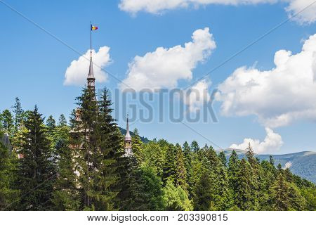 Peles castle behind the trees at Carpathian mountains summer residence of Romanian royal family.