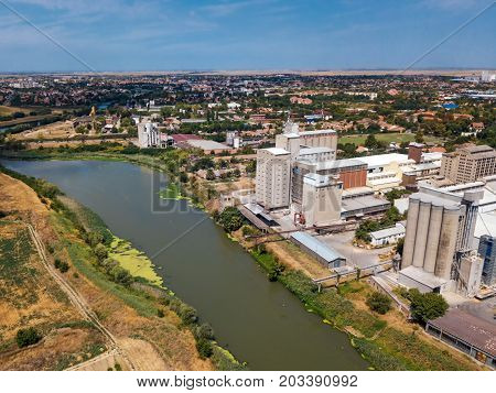 Aerial drone pov view of industrial cityscape with factory buildings and warehouses