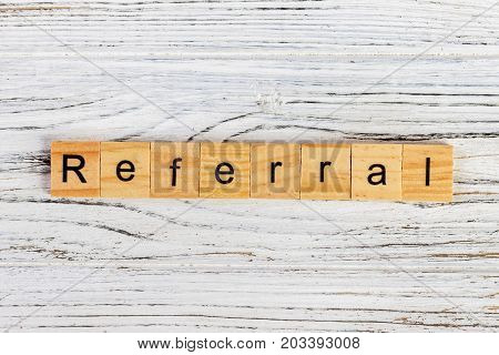 REFERRAL word made with wooden blocks concept