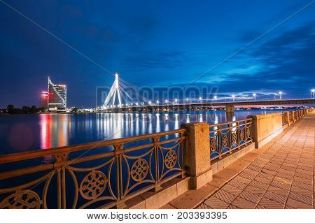 Riga, Latvia - July 01, 2016: View Of Famous Vansu Cable-Stayed Bridge In Bright Night Illumination From The Deserted Embankment Of The Daugava Or Western Dvina River Under Dramatic Blue Summer Sky.