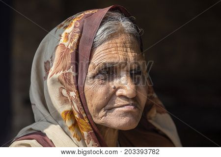 VARANASI INDIA - JANUARY 25 2017 : Portrait old beggar woman on street at Dashashwamedh Ghat in Varanasi Uttar Pradesh India