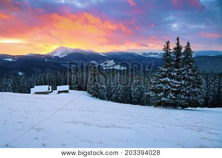 Picturesque winter landscape with huts snowy mountains and sunrise. Winter landscape for leaflets.