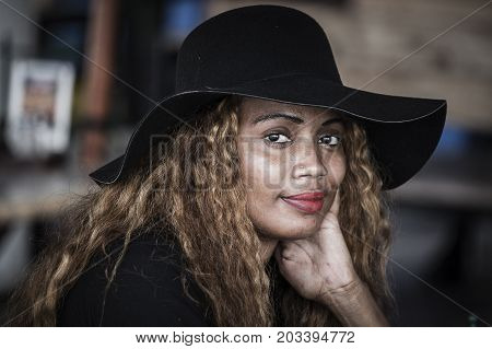 PORT LOUIS MAURITIUS - MARCH 06 2017 : Portrait of a local woman with a black hat smiling at the market in Port Louis island Mauritius