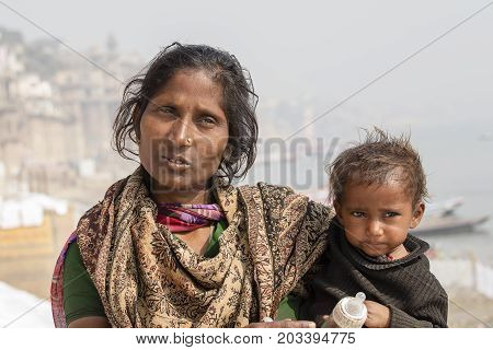 VARANASI INDIA - JANUARY 26 2017 : Portrait mother and children on the street at the ghats of Varanasi Uttar Pradesh India