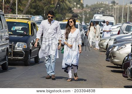 MUMBAI INDIA - JANUARY 29 2017 : Unknown man and woman walking along a busy road. Street scene in an expensive area of Mumbai India