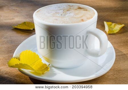 Cappuccino or coffee latte with foam in white cup and the Inscription Good Morning on wooden table. Autumn concept.