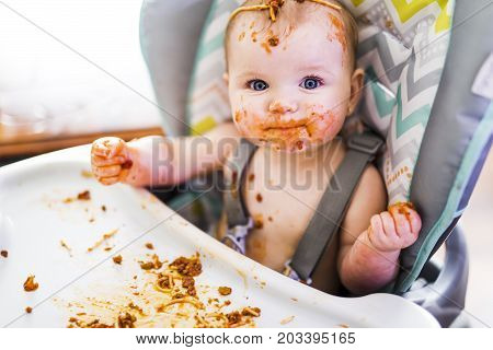 A Little baby eating her dinner and making a mess