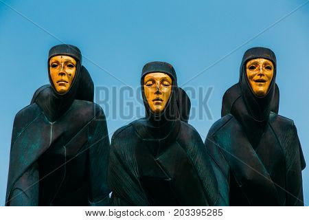 Vilnius, Lithuania, Eastern Europe - July 7, 2016: Close Up Of Black Sculpture Of Three Muses On Facade Of Lithuanian National Drama Theatre Building, Main Entrance, Blue Evening Sky Background.