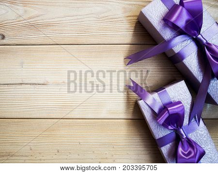 Gift boxes with purple ribbons on wooden board. Holidays concept