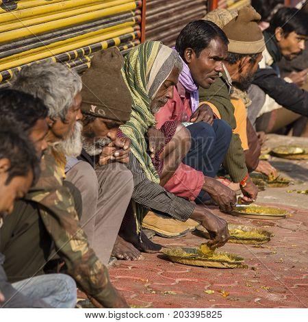VARANASI INDIA - JANUARY 25 2017 : Unidentified poor indian people eating free food at the street near river ganges in Varanasi India