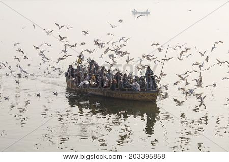 VARANASI INDIA - JANUARY 26 2017 : Unknown indian people are in a wooden boat that sailed on the Ganges River morning in Varanasi. Uttar Pradesh India