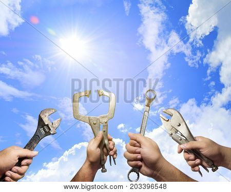The hands of many mechanic holding instruments with blue sky backgroundclouds and sun in the daytime. Mechanic success and Tools concept.Adjustable wrenchLocking pliersC-Clamp PliersRatchet wrench