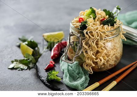 Chinese or asian noodles with vegetables in jar fast lunch asian food with chopsticks
