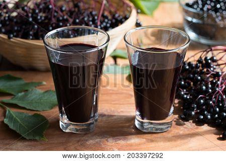 Two glasses of elderberry syrup on a wooden table with fresh elderberries in the background
