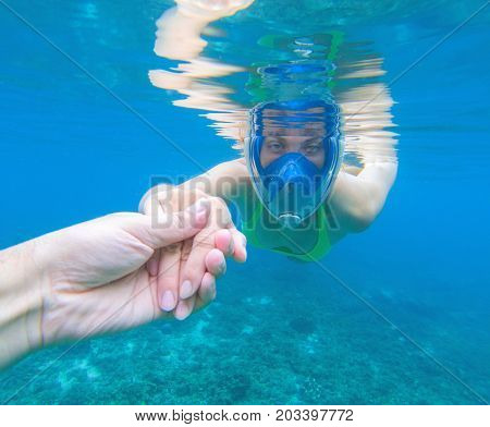 Snorkeling woman in full-face snorkeling mask. Swimming girl holds hand of partner. Romantic underwater photo. Snorkeling lesson. Sea water sport. Coral reef snorkeling. Swimming woman guiding by hand