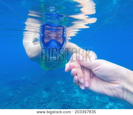 Snorkeling woman in full-face snorkeling mask. Swimming girl holds hand of partner. Romantic underwater photo. Snorkeling lesson. Sea water sport. Coral reef snorkeling. Snorkel guiding by hand
