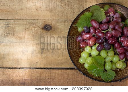 Plate of red and white grapes on a wooden surface