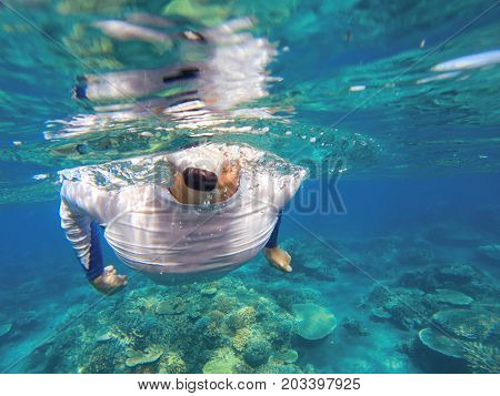 Young man underwater with marine flora. Male snorkel in tropical lagoon undersea photo. Snorkeling in coral reef. Tropical sea activity. Water sport. Tropical coral reef. Strong man body in sea water