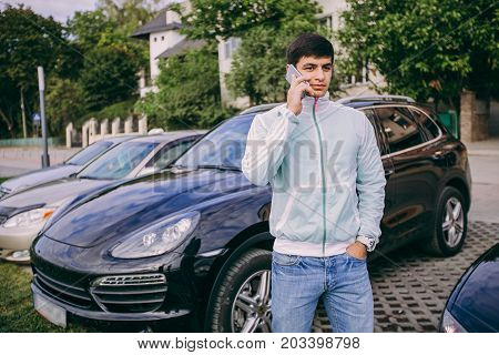 man stands near a black car with a telephone in hands