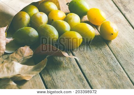 Ripe organic colorful yellow and green plums in brown craft paper bag scattered on plank wood background. Dry leaves. Soft natural light. Autumn fall harvest thanksgiving. Tranquility copy space.