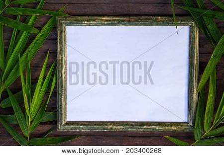 Blank paper and bamboo flat lay on wooden background. Natural rustic photo frame with blank place for text. Green bamboo leaf on table. Exotic vacation top view. Wood frame with tropical floral decor