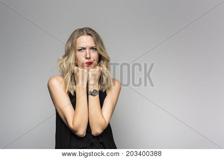 Emotional young pretty girl with long blond hair in anger. Portrait of a woman on a gray background.