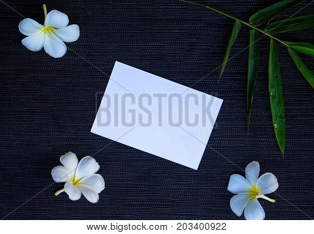 Flat lay with white paper and green bamboo. Blank white postcard mockup. Tropical travel. Exotic flower flat lay. White frangipani flowers. Green bamboo leaf. Tropic natural banner. Wedding invitation