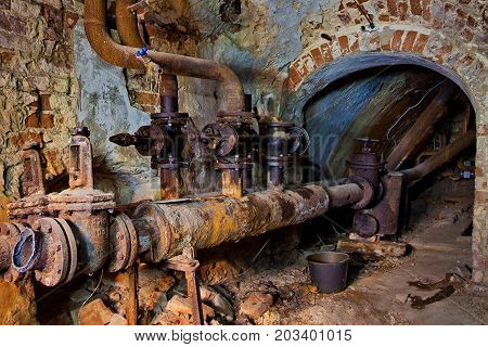 Underground vaulted cellar of red brick with rusty water heating pipes.