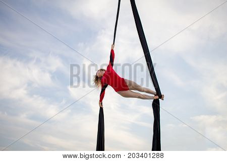 girl in skinny wear performing a dance on the black ribbons against the sky,  gymnast performing aerial exercise