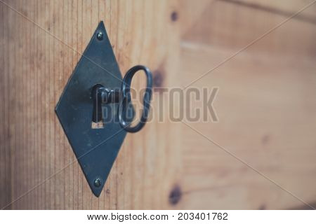 old key in keyhole wooden drawer closeup