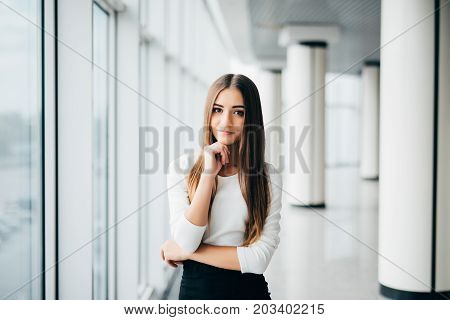 Attractive Young Businesswoman Portrait With Hands On Chin Near Office Windows