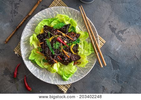 Asian stir-fry liver with bell pepper, carrots and onion. With greens and rice.