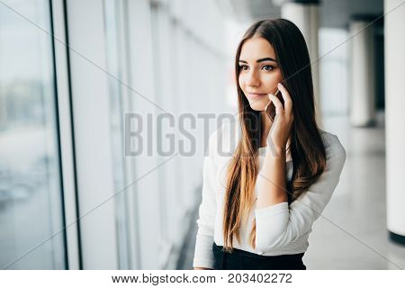 Happy Businesswoman Standing In Her Office In A Highrise Building Overlooking The Cityscape. Busines