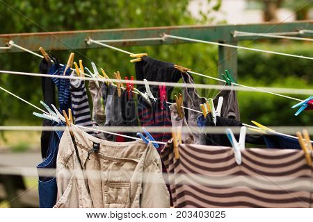 Several washing lines with damp clothing on old rusty outdoor stand