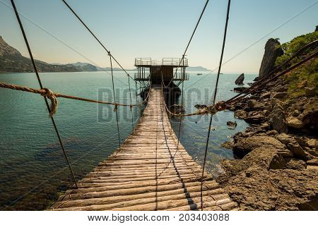 Suspension Bridge Over Water To A House On The Water