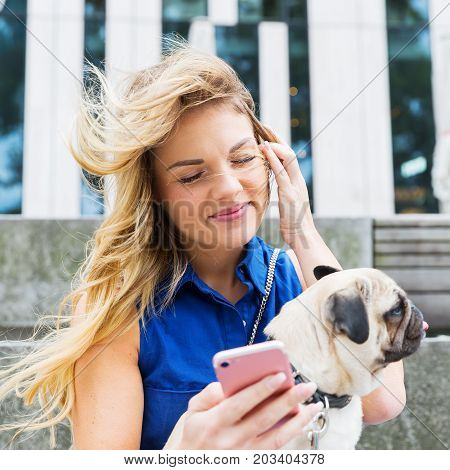 Woman With Pug Handles A Smartphone