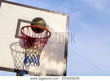 Basketball game outdoor equipment. Basket and ball. Accurate ball throw in basket. Street basketball. School holiday activity. Basketball competition victory. Basketball game on summer. Active playing