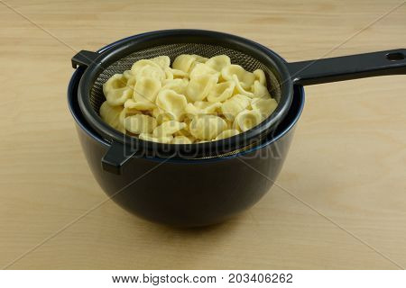 Boiled cooked orecchiette baby ears pasta draining in strainer in blue bowl