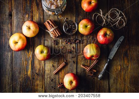Red Apples with Scattered Clove Cinnamon and Anise Star. Candy Sugar and Some CLove in a Jar. Ingredients for Prepare Christmas Drink