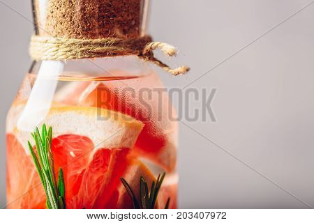 Part of Bottle with Grapefruit and Rosemary infused Water. Close up. Copy Space on the Right.