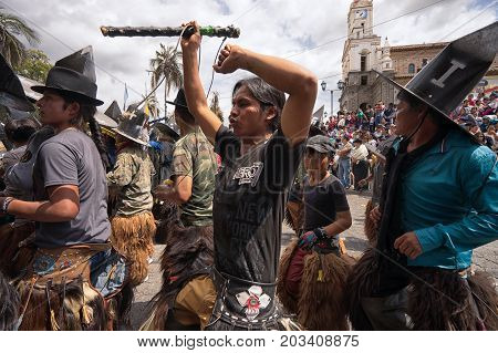 July 24 2017 Cotacachi Ecuador: indigenous kichwa men dancing on the street at Inti Raymi celebration
