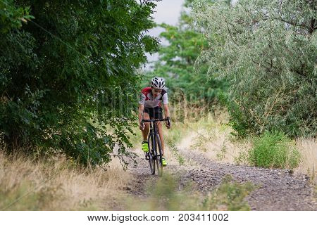 Biycle rider on cyclocross bike training outdoor on gravel  country road
